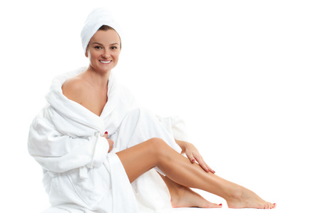 Beautiful girl in bathrobe is touching her smooth legs. Spa, depilation and bodycare concept