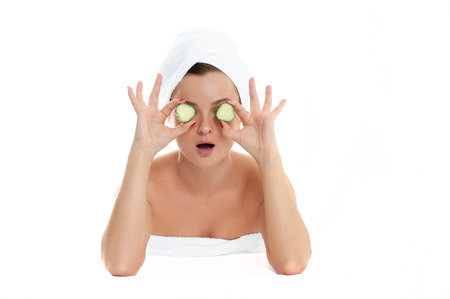 Beautiful young woman with clean fresh skin is holding two slice cucumber. Mask. Facial treatment, beauty and spa .