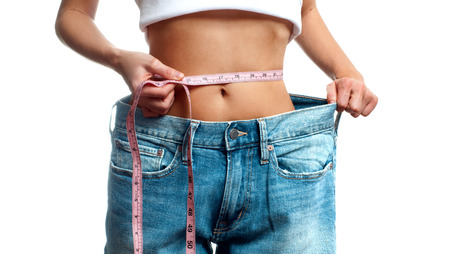 Woman is measuring waist after weight loss, diet concept. Woman in oversize jeans Stock Photo