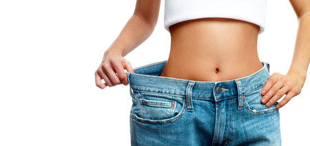 Woman is measuring waist after weight loss, diet concept. Woman in oversize jeans 스톡 콘텐츠