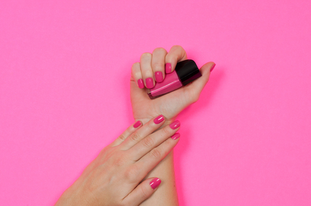 Nail care and manicure. Beautiful female hands with pink nail polish Фото со стока