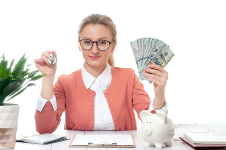 Business woman or real estate agent showing keys and bunch of money banknotes Stok Fotoğraf