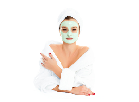 Beautiful woman in bathrobe is getting facial clay mask. Beauty, cosmetics, body care and spa concept