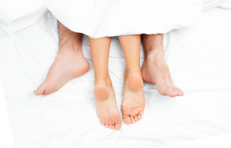 Close up of the feet of a couple on the bed. Loving couple is lying on bed under blanket