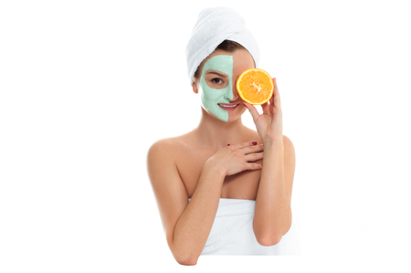 Beautiful woman is getting facial clay mask on white background. Beauty, body care and spa concept
