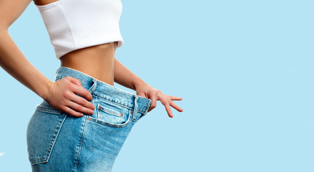 Diet concept and weight loss. Woman in oversize jeans on pastel blue background