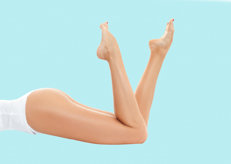 Beautiful long woman's legs with smooth skin after depilation on pastel background. Banque d'images