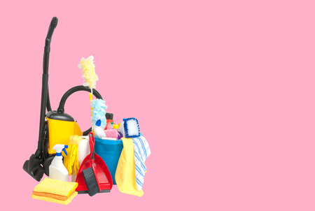 Variety of cleaning products in  bucket  and vacuum cleaner on pastel pink background