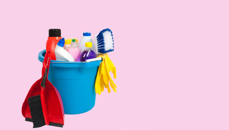 Variety of cleaning products in  bucket on pastel pink background