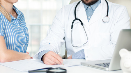 Doctor is talking with woman patient and making notes while sitting in his office