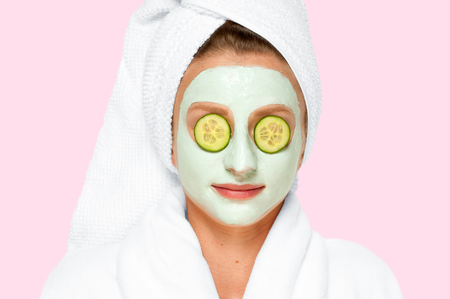Beautiful young woman is getting facial clay mask with cucumbers on eyes on faded pastel background