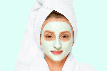 Treatment in spa salon. Beautiful young woman with cosmetic clay mask on face. Faded pastel color Imagens
