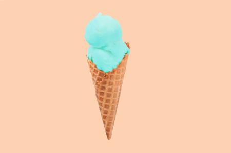 Pistachio ice cream cone on faded pastel color background. Ice cream in wafer cup. Foto de archivo