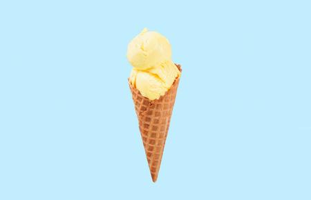 Vanilla ice cream cone on blue faded pastel color background. Vanilla ice cream in wafer cup.