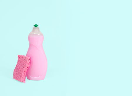 Detergents and sponge for dishes on pastel green background Banco de Imagens