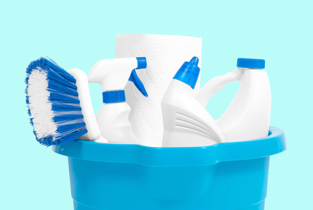 Variety of cleaning products in bucket on pastel green background