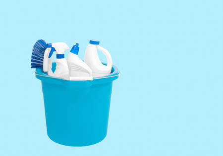 Variety of cleaning products in bucket on pastel blue background