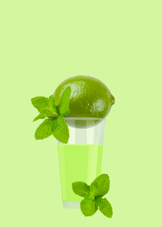 Glass of lime juice with ripe lime on pastel green background