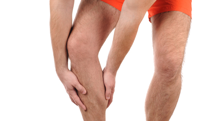 Man with pain in knee. Athlete in sports shorts clutching his legs muscles