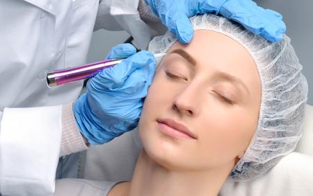 Microblading cejas. Cosmetóloga haciendo maquillaje permanente. Mujer atractiva que consigue cuidado facial y tatuaje en el salón de belleza Foto de archivo