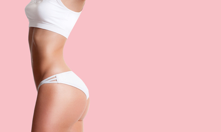 Beautiful slim woman with perfect sporty body. Successful weight loss on pink background