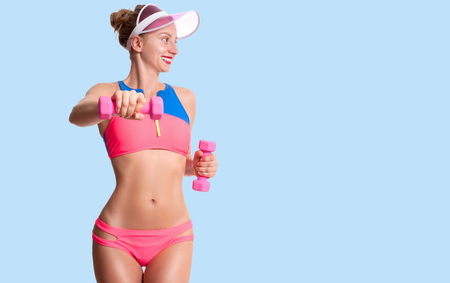 Fitness. Exercising. Beautiful woman with perfect sporty body is holding dumbbells on blue background