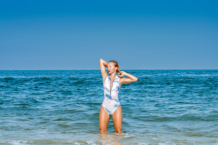 Summer vacation. Beautiful tanned woman in swimsuit is coming out of the ocean on tropical beach Stock Photo