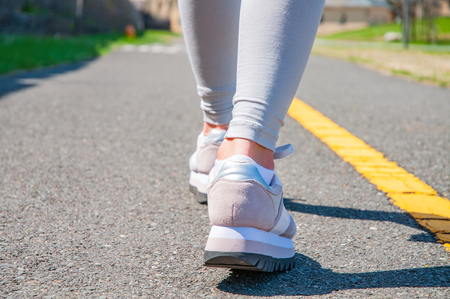 Walking. Close-up of women's running shoes on a paved trail. Female feet in sneakers. 免版税图像