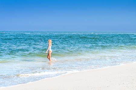 Summer vacation. Beautiful tanned woman in swimsuit is walking on the ocean beach Stock Photo