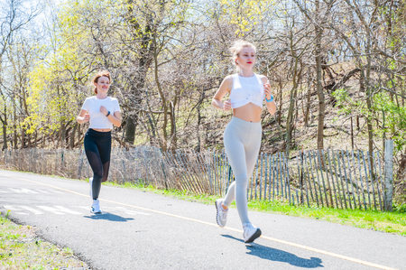 Running.Two women exercising by jogging in the park. Female fitness training outside.