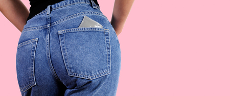 Condoms in package in back jeans pocket. Woman in jeans putting a condom a pocket.