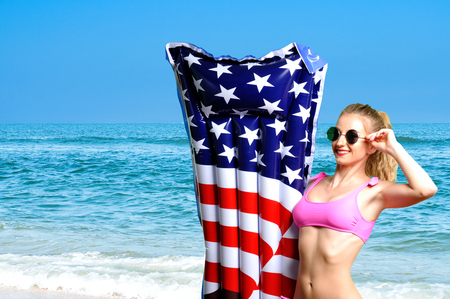 Summer Vacation. Enjoying suntan woman in bikini with inflatable mattress american  flag on the beach.