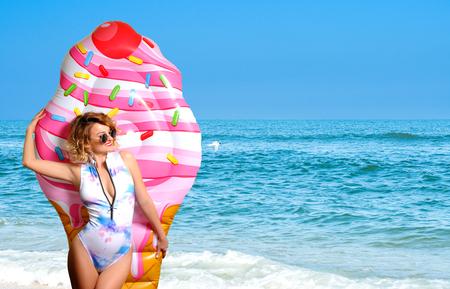 Summer Vacation. Enjoying suntan woman in bikini with inflatable mattress ice cream on the beach.