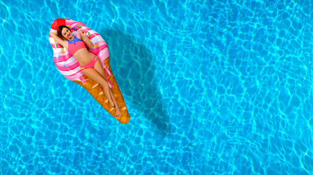 Summer Vacation. Enjoying suntan Woman in bikini on the inflatable mattress in the swimming pool. Stockfoto - 103326795