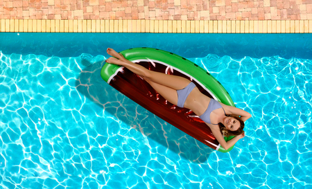 Summer Vacation. Enjoying suntan Woman in bikini on the inflatable mattress in the swimming pool. Stockfoto