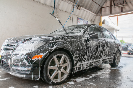 Car washing. Cleaning modern car covered by foam. Stock Photo