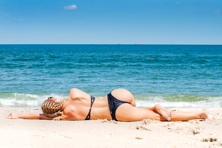 Beautiful slim woman in bikini lying on sand and tanning on the beach