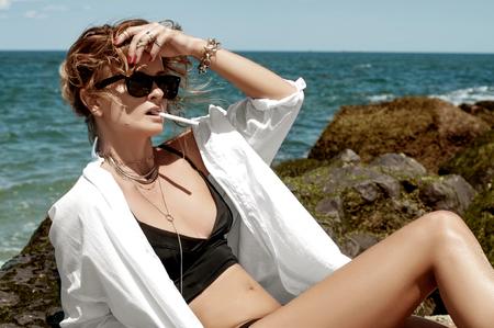 Beautiful fashion woman in bikini is smoking on the beach