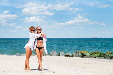 Happiness moment. Two Attractive women in bikini on the beach. Best friends having fun, summer vacation holiday lifestyle. Stock Photo
