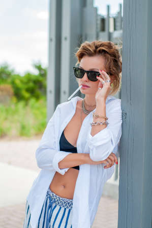 Stylish beautiful woman with jewelry bracelets and rings in summer clothes smoking in the street 스톡 콘텐츠