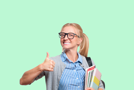 Happy young student girl holding books, high school or college graduand on green background. Back to school Archivio Fotografico