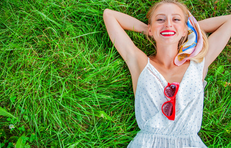 Hermosa mujer feliz se encuentra en la hierba. Niña sonriente relajarse al aire libre en verano. Vista desde arriba.
