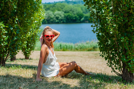 Beautiful happy woman on the grass relaxing outdoors in summer. Stock Photo