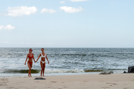 Happiness moment. Two attractive women in bikini on the beach. Best friends having fun, summer vacation holiday lifestyle Foto de archivo