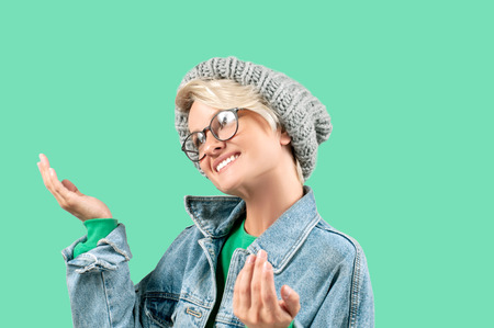 Portrait of happy beautiful woman in fashionable jeans jacket and hat on green background.