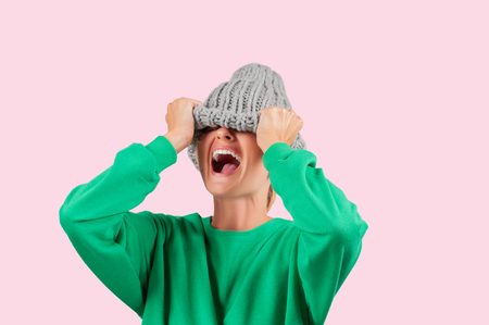 Furious. Emotional angry woman is pulling wool hat over her eyes on pink background