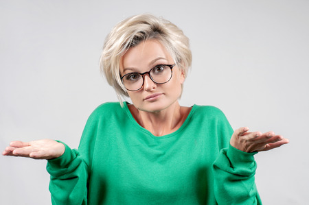 Human emotions and feeling concept. Puzzled hesitant woman shrugs shoulders expressing uncertainty. Stock Photo