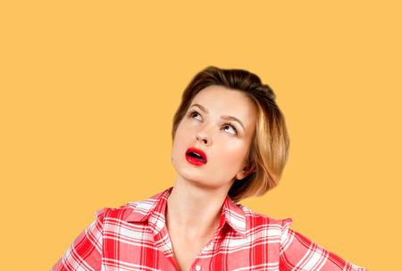 Thinking business woman with questioning face expression looking up on yellow background