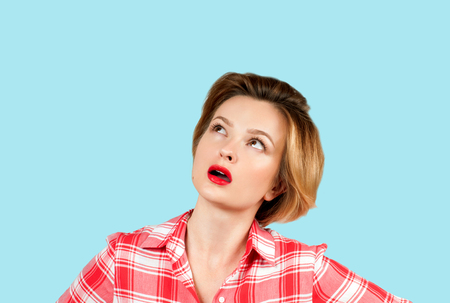 Young thinking business woman with questioning face expression looking up on blue background