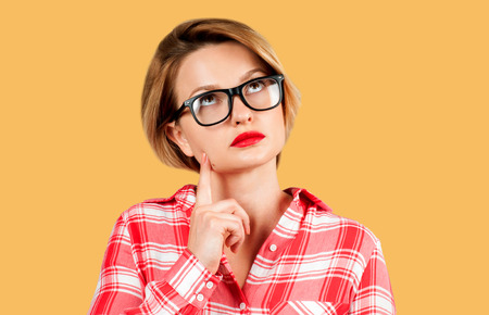 Young thinking business woman with questioning face expression looking up on yellow background